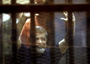 Former Egyptian President Mohamed Mursi reacts behind bars with other Muslim Brotherhood members at a court in the outskirts of Cairo